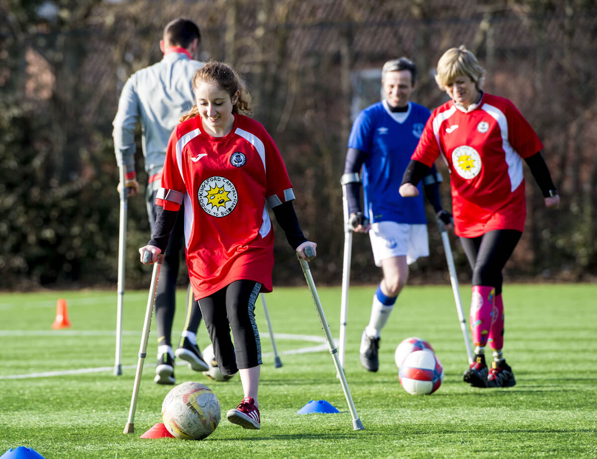 Amputee footballer using crutches