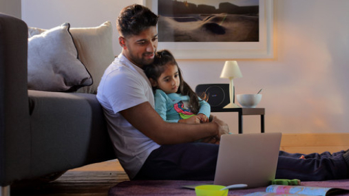 Father sat on the floor with his daughter on his knee, happily looking at a computer screen.